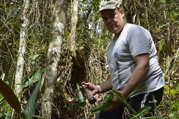 Pedro recolhendo garrafas de lixo na trilha (Fotos: Henrique Pinheiro)