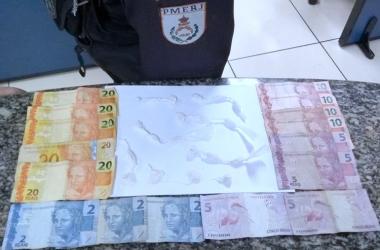 Os entorpecentes e o dinheiro apreendidos na incursão foram apresentados na Delegacia Legal de Cantagalo (Foto: 11º BPM)