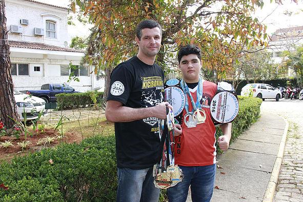Pai e filho são lutadores e mostram suas medalhas (Divulgação Daniel Marcus/ PMNF)