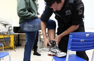 Policial bota tornozeleira em um preso em regime semiaberto (Foto: Agência Brasil)