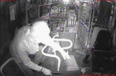 Imagem da câmera do ônibus mostra o assaltante tirando dinheiro do caixa (Reprodução de vídeo)